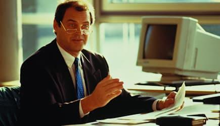 Portrait of male executive sitting at desk holding document,talking