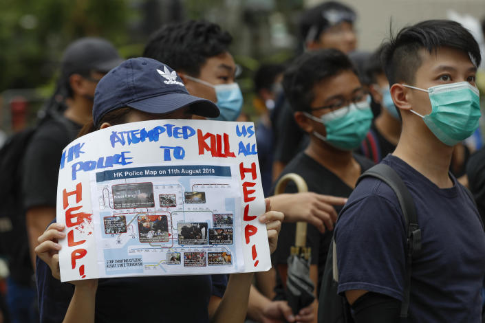 A protester displays a placard during a march organized by a pro-democracy group in Hong Kong Saturday, Aug. 17, 2019. Another weekend of protests is underway in Hong Kong as Mainland Chinese police are holding drills in nearby Shenzhen, prompting speculation they could be sent in to suppress the protests. (AP Photo/Vincent Thian)