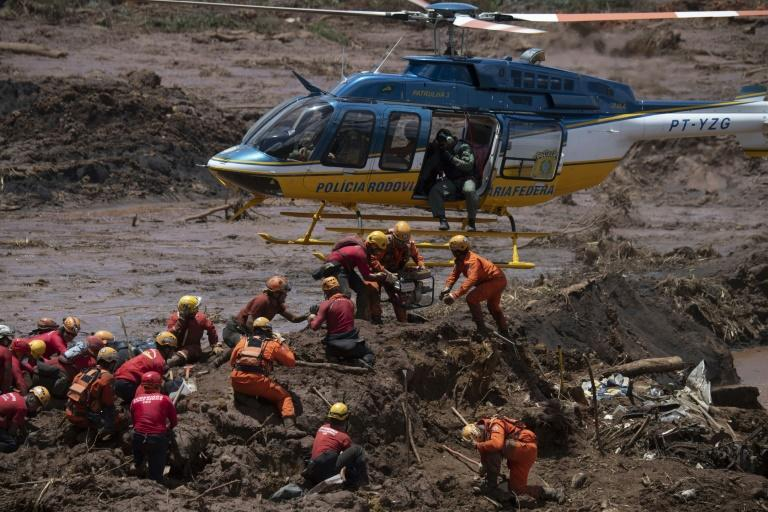 Firefighters search for victims of the 2019 dam collapse at an iron-ore mine belonging to Brazil's giant mining company Vale -- which has agreed to pay $7 billion in damages