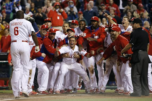 Philadelphia Phillies players celebrate and wait for Ryan Howard, left, to cross home plate after Howard's game-winning three-run home run off Colorado Rockies relief pitcher Boone Logan during the ninth inning of a baseball game, Wednesday, May 28, 2014, in Philadelphia. Philadelphia won 6-3. (AP Photo/Matt Slocum)