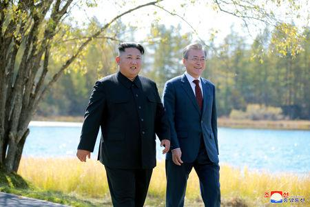 FILE PHOTO - South Korean President Moon Jae-in and North Korean leader Kim Jong Un walk during a luncheon