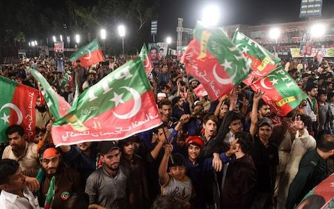 Supporters of Pakistani cricket star-turned-politician and head of the Pakistan Tehreek-e-Insaf (PTI) Imran Khan (unseen) gather at his political campaign rally - Credit: AFP