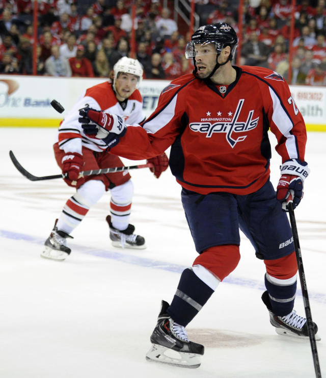 Washington Capitals right wing Troy Brouwer, front, eyes the puck against Carolina Hurricanes defenseman Justin Faulk, rear, during the first period an NHL hockey game, Thursday, Oct. 10, 2013, in Washington. (AP Photo/Nick Wass)