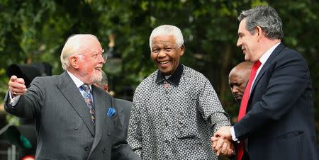 Britain's then Prime Minister Gordon Brown (R) and director Richard Attenborough assist South Africa's former President Nelson Mandela (C) to the podium, during the unveiling ceremony of a statue in Mandela's honour in London's Parliament Square, in this file picture taken August 29, 2007. REUTERS/Daniel Berehulak