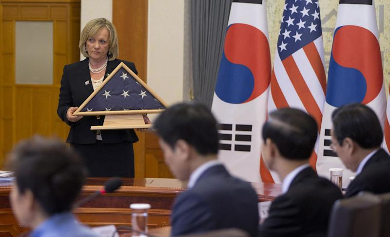 An American flag is presented with South Korean national flags during a bilateral meeting between U.S. President Barack Obama and South Korean President Park Geun-hye at the Blue House, Friday, April 25, 2014, in Seoul, South Korea, as gesture to the families of the victims of the ferry disaster in the water off the country's southern coast. It was flown over the White House on the same day of the Sewol sinking, Obama said. (AP Photo/Carolyn Kaster)
