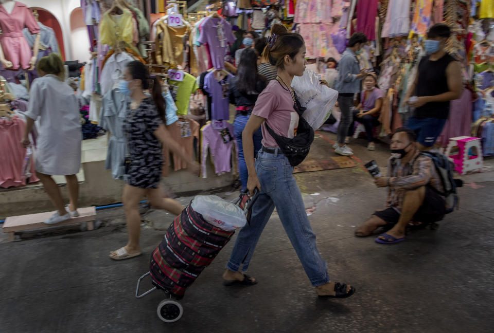 FILE - In this Aug. 6, 2020, file photo, a shopper pulls a cart full of clothing at a market in Bangkok, Thailand. Shortages of power, computer chips and other parts, soaring shipping costs and shutdowns of factories to battle the pandemic are taking a toll on Asian economies. (AP Photo/ Gemunu Amarasinghe, File)
