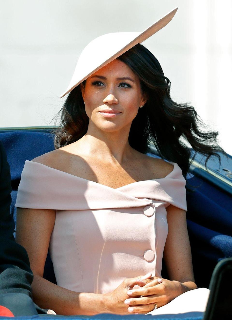 """<p>When the Duchess of Sussex joined the royal family for the first time on the balcony of Buckingham Palace for the annual Trooping of the Colour, not everyone was thrilled with her blush Carolina Herrera ensemble. Many <a href=""""https://people.com/royals/meghan-markle-trooping-the-colour-dress/"""" rel=""""nofollow noopener"""" target=""""_blank"""" data-ylk=""""slk:etiquette experts thought"""" class=""""link rapid-noclick-resp"""">etiquette experts thought</a> the royal should have chosen a more modest neckline for the traditional ceremony. </p>"""