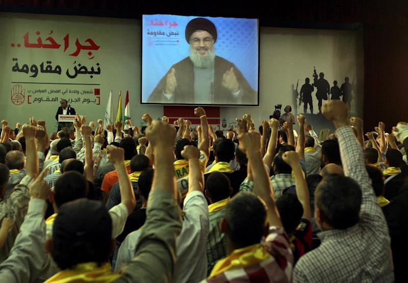 "Hezbollah supporters raise their hands in salute as Hezbollah leader Sheik Hassan Nasrallah speaks on a screen via a video link from a secret place, during a rally to mark the ""wounded resistants day,"" in the southern suburb of Beirut, Lebanon, Friday, June 14, 2013. Nasrallah said his group will continue to fight in Syria ""wherever needed,"" and said he has made a ""calculated"" decision to defend Syria and is ready to bear all consequences.(AP Photo/Bilal Hussein)"