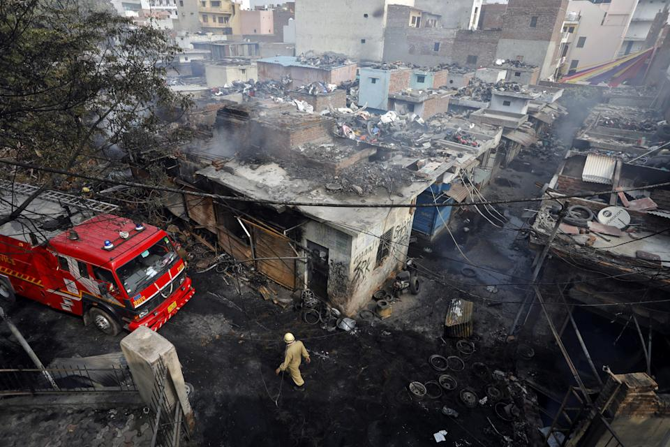 A firefighter walks past damaged shops at a tyre market after they were set on fire by a mob in a riot affected area after clashes erupted between people demonstrating for and against a new citizenship law in New Delhi, India, February 26, 2020. REUTERS/Adnan Abidi