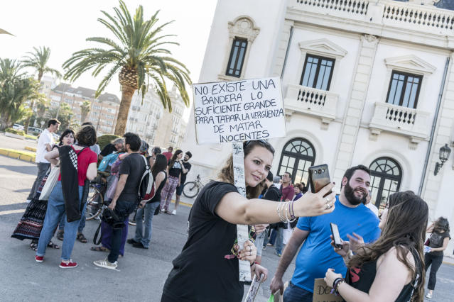 """<p>A woman takes a selfie holding a sign """"There is no large enough flag to cover the shame of killing innocents"""" in support of the refugees. (Photo: José Colón for Yahoo News) </p>"""