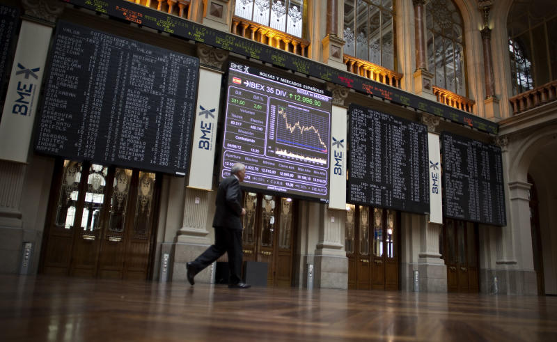 A man walks pass to the main display at the Stock Exchange in Madrid, Spain, Monday, June 4, 2012.  The Labor Ministry reported today a drop of 30,313 people claiming benefits, to a total of 4,71 million unemployed people in May, a traditionally good month for hiring as companies prepare for the vacation season. (AP Photo/Alberto Di Lolli)