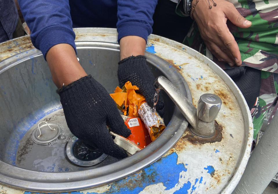 Indonesian navy personnel inspect a part the flight data recorder recovered at the crash site of the Sriwijaya Air flight SJ-182 at the Tanjung Priok Port, Tuesday, Jan. 12, 2021. Indonesian navy divers searching the ocean floor on Tuesday recovered the flight data recorder from a Sriwijaya Air jet that crashed into the Java Sea with 62 people on board, Saturday, Jan. 9, 2021. (AP Photo/Fadlan Syam)