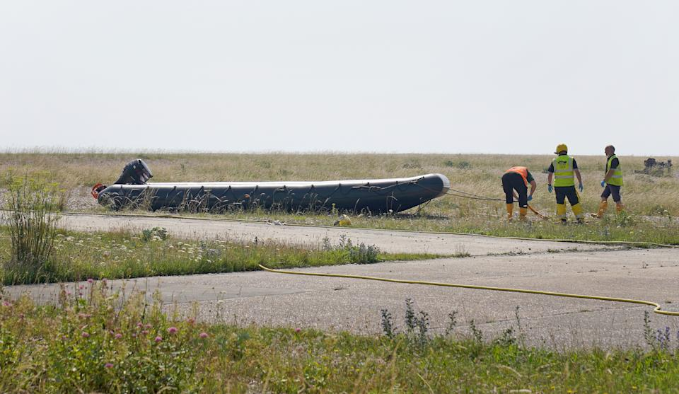 A boat used by a group of people thought to be migrants crossing from France is towed from the beach at Dungeness, Kent, following a small boat incident in the Channel. Picture date: Tuesday July 20, 2021.