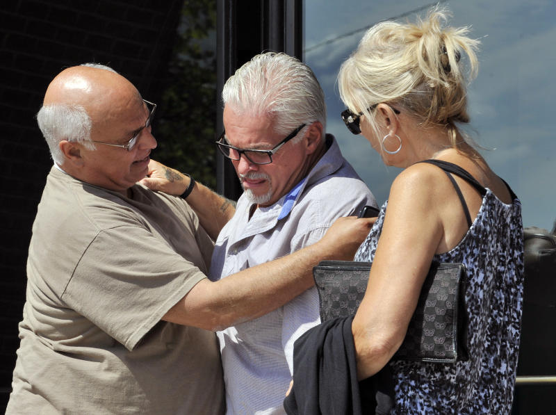 """In this photo made Aug. 12, 2013, Steven Davis, brother of slain Debra Davis, center, is comforted by Skip Marcella, left, after speaking outside federal court in Boston where a jury found James """"Whitey"""" Bulger guilty on several counts of murder, racketeering and conspiracy. Jurors could not agree whether Bulger was involved in Debra Davis' killing. When Bulger is sentenced this week, family members of eight slaying victims are hoping a judge will let them speak, even though Bulger was acquitted in those deaths. (AP Photo/Josh Reynolds, File)"""