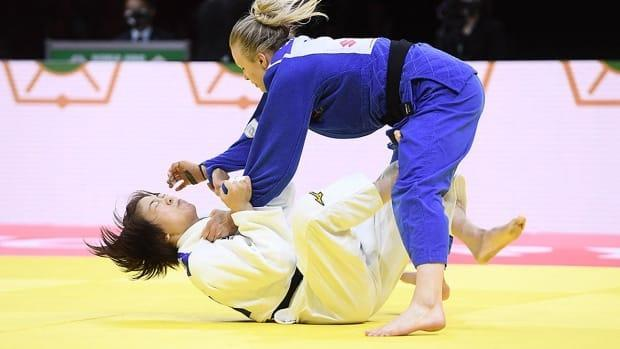 Jessica Klimkait, right, of Whitby, Ont., defeated Japan's Momo Tamaoki, left, in the under-57 kg women's final at the judo world championships on Tuesday in Budapest, Hungary. Klimkait joins Christa Deguchi as Canada's only world champions in the sport. (Attila Kisbenedek/AFP via Getty Images - image credit)