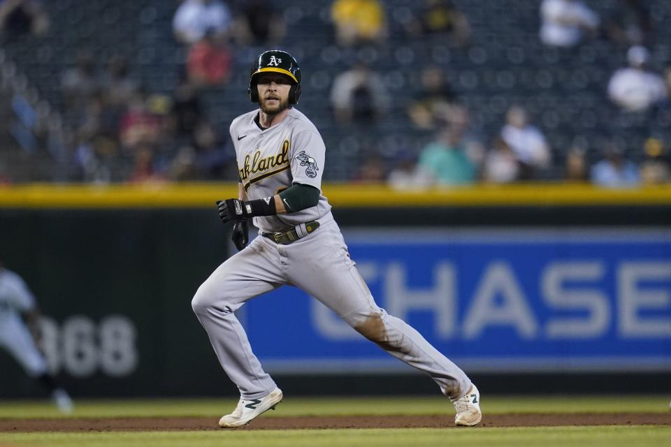 Oakland Athletics' Jed Lowrie runs to third base against the Arizona Diamondbacks during the third inning of a baseball game Tuesday, April 13, 2021, in Phoenix. (AP Photo/Ross D. Franklin)