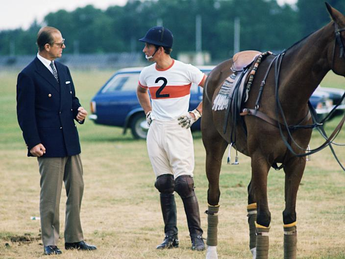 Prince Charles, wearing a polo outfit, stands next to a horse as he talks to Prince Philip
