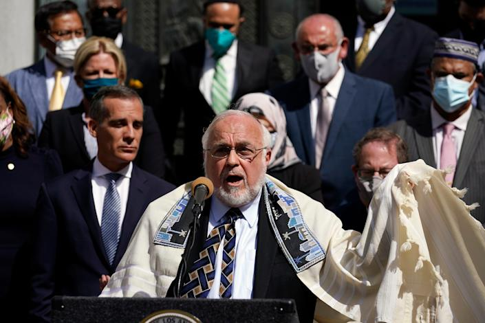 Rabbi Abraham Cooper, center, of the Simon Wiesenthal Center, speaks in front of civic and faith leaders outside City Hall, Thursday, May 20, 2021, in Los Angeles. Faith and community leaders in Los Angeles called for peace, tolerance and unity in the wake of violence in the city that is being investigated as potential hate crimes.