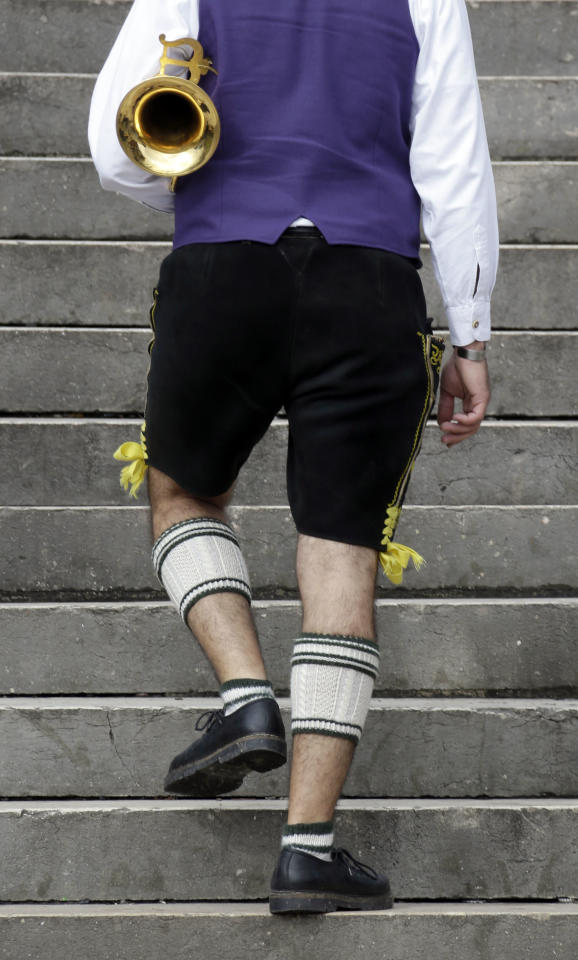 A musician of the Oktoberfest orchestra arrives for the famous Oktoberfest beer festival concert in Munich, southern Germany, Sunday, Sept. 30, 2012. The world's largest beer festival, to be held from Sept. 22 to Oct. 7, 2012 will see some million visitors. (AP Photo/Matthias Schrader)