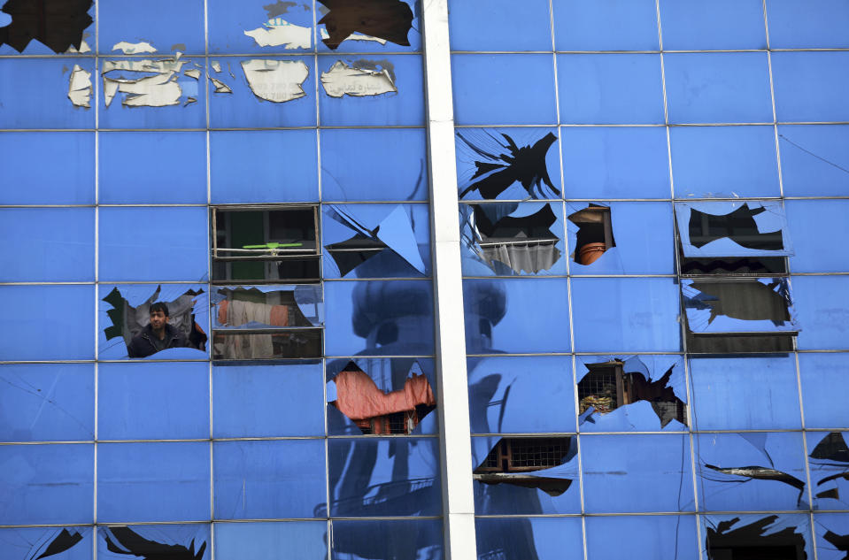 An Afghan man looks through a damaged window after a bombing attack in Kabul, Afghanistan, Sunday, Dec. 20, 2020. The strong car bomb explosion rocked the capital Kabul city on Sunday morning, killing multiple people, said a government official. (AP Photo/Rahmat Gul)