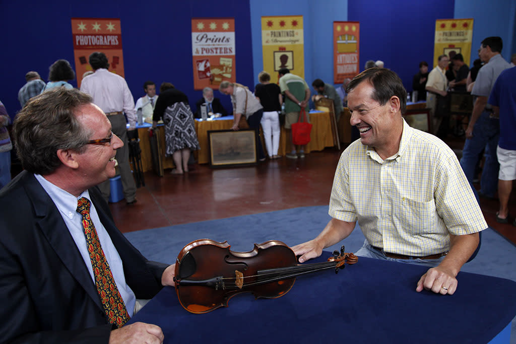 Appraiser Peter Shaw (left) with a guest and his 1922 Giuseppe Pedrazzini violin. The violin was found in a dumpster and valued at $35,000.