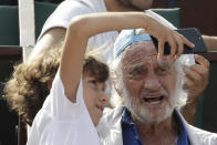 FILE - In this June 8, 2018 file photo, a child takes a selfie with French actor Jean-Paul Belmondo during the semifinal match at the French Open tennis tournament between Spain's Rafael Nadal and Argentina's Juan Martin Del Potro at the Roland Garros stadium in Paris. French New Wave actor Jean-Paul Belmondo has died, according to his lawyer's office on Monday Sept. 6, 2021. (AP Photo/Alessandra Tarantino, File)