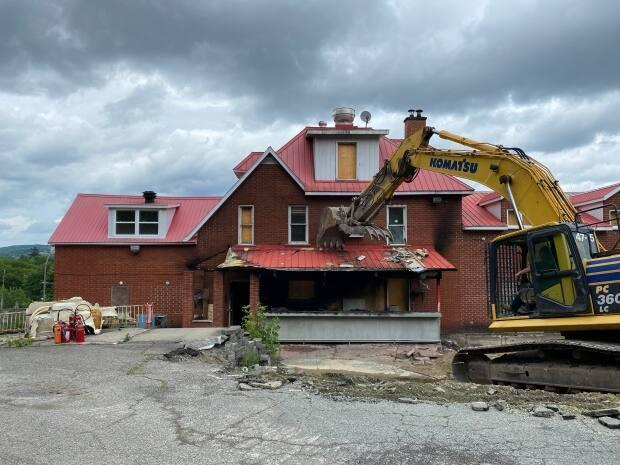An excavator starts demolishing the former Hells Angels' bunker by ripping down the back patio. (Spencer Van Dyk/CBC - image credit)