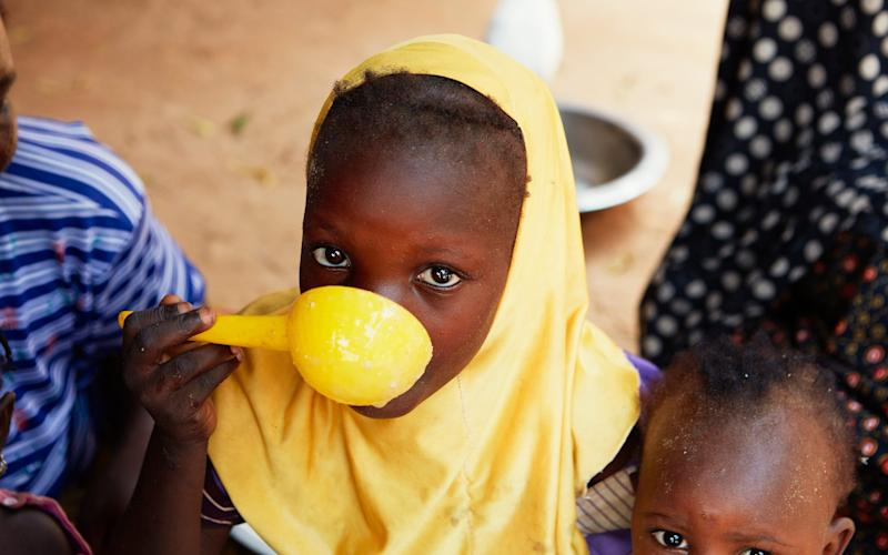 A young girl shares a meal with her siblings in Kietche Village, Niger - Yuki Sugiura/British Red Cross