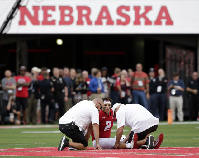 Nebraska trainers tend to the leg of injured quarterback Adrian Martinez (2) during the second half of an NCAA college football game against Colorado in Lincoln, Neb., Saturday, Sept. 8, 2018. Colorado won 33-28. (AP Photo/Nati Harnik)