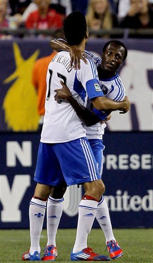 Montreal Impact defender Dennis Iapichino (17) celebrates with midfielder Sanna Nyassi, right, after Nyassi scored in the first half of an MLS soccer match against the New England Revolution, in Foxborough, Mass., Sunday, Aug. 12, 2012. The Impact won 1-0. (AP Photo/Steven Senne)