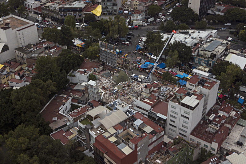 FILE - This Sept. 23, 2017 file photo shows the site of the earthquake-collapsed office building on Alvaro Obregon Avenue in the Roma Norte neighborhood of Mexico City. The city government is taking ownership of the lot where the seven-story office building collapsed in September's deadly earthquake, clearing the way for a planned park memorializing victims of the disaster. Forty-nine people died in the building when it collapsed Sept. 19. (AP Photo/Miguel Tovar, File)