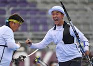 <p>South Korea archery star's Kim Je-deok fist bumps teammate Oh Jin-hyek as they become gold medalists following their men's team gold medal match against Taiwan at Yumenoshima Park Archery Field on July 26.</p>