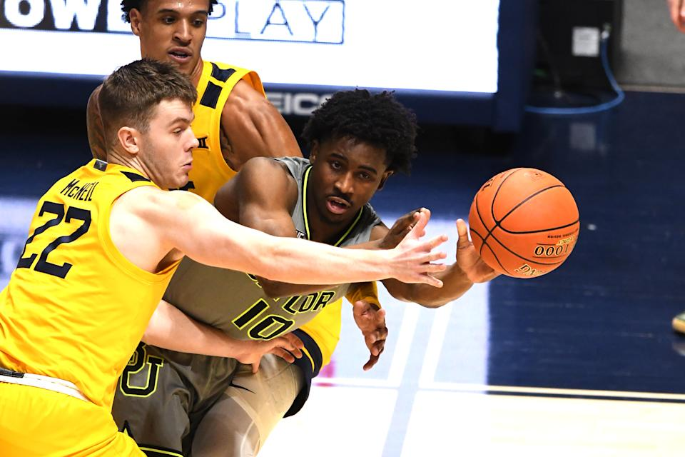 Adam Flagler #10 of the Baylor Bears passes the ball around Sean McNeil #22 of the West Virginia Mountaineers in the second half during a college basketball game at WVU Coliseum  on March 2, 2021 in Morgantown, West Virginia.  (Photo by Mitchell Layton/Getty Images)