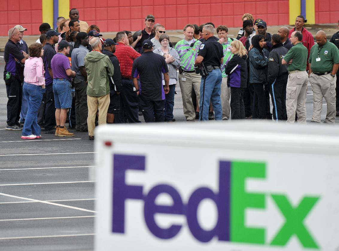 "A Cobb County Police Officer speaks to FedEx employees and family members gathered at the parking lot of a skating rink located near the shipping facility where a gunman open fire in Kennesaw, Ga., on Tuesday, April 29, 2014. A shooter described as being armed with an assault rifle and having bullets strapped across his chest ""like Rambo"" opened fire Tuesday morning at a FedEx station outside Atlanta, wounding at least six people before police found the suspect dead from an apparent self-inflicted gunshot. (AP Photo/Atlanta Journal-Constitution, Brant Sanderlin) MARIETTA DAILY OUT; GWINNETT DAILY POST OUT; LOCAL TV OUT; WXIA-TV OUT; WGCL-TV OUT"