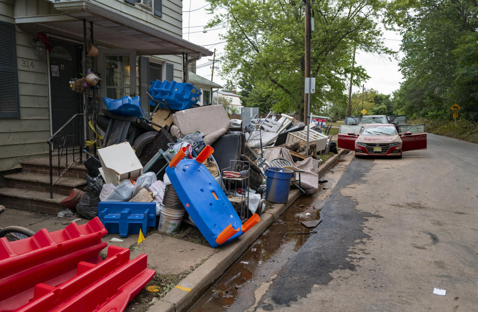 Debris from flood damage caused by the remnants of Hurricane Ida lies on the side of a street in Manville, N.J., Sunday, Sept. 5, 2021. Flood-stricken families and business owners across the Northeast are hauling waterlogged belongings to the curb and scraping away noxious mud as cleanup from Ida moves into high gear. (AP Photo/Craig Ruttle)
