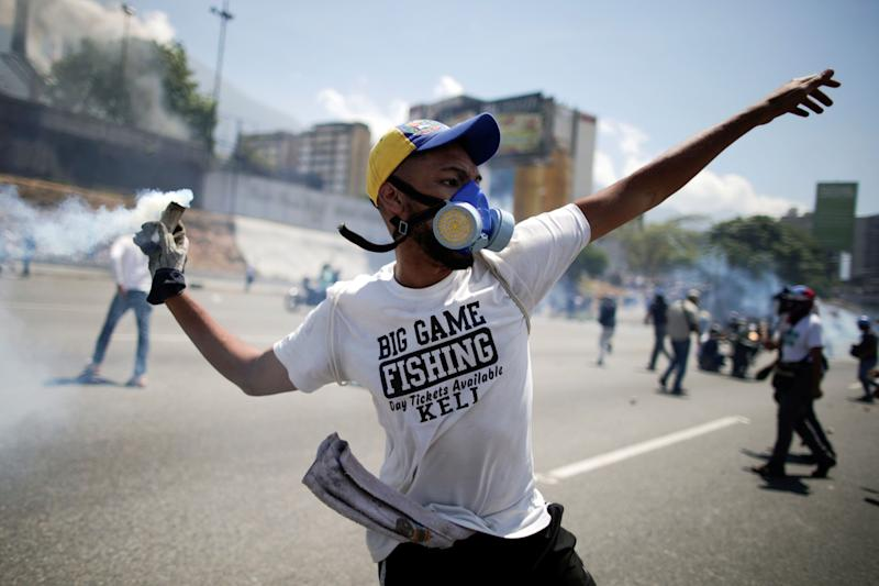 "An opposition demonstrator throws back a tear gas canister on a street near the Generalisimo Francisco de Miranda Airbase ""La Carlota"" in Caracas, Venezuela April 30, 2019. (Photo: Ueslei Marcelino/Reuters)"