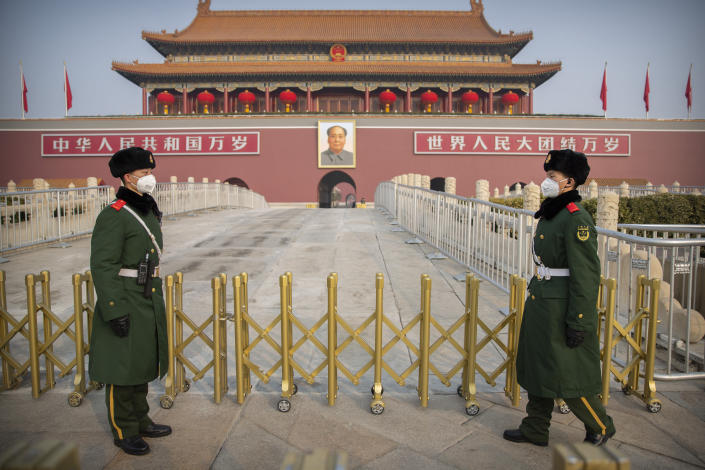 Paramilitary police wear face masks as they stand guard at Tiananmen Gate adjacent to Tiananmen Square in Beijing, Monday, Jan. 27, 2020. China on Monday expanded sweeping efforts to contain a viral disease by postponing the end of this week's Lunar New Year holiday to keep the public at home and avoid spreading infection. (AP Photo/Mark Schiefelbein)
