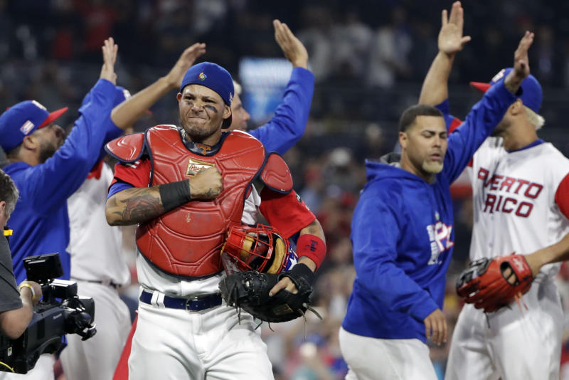 Puerto Rico catcher Yadier Molina, center left, reacts with teammates after defeating the Dominican Republic in a second-round World Baseball Classic game Tuesday, March 14, 2017, in San Diego. Puerto Rico won, 3-1. (AP Photo/Gregory Bull)