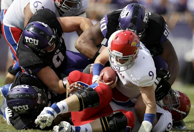 Kansas quarterback Jake Heaps (9) lands on top of offensive linesman Pat Lewandowski, bottom, after being sacked by TCU 's Davion Pierson, bottom left, Jon Koontz, top left, and Terrell Lathan (90) in the first half of an NCAA college football game, Saturday, Oct. 12, 2013, in Fort Worth, Texas. (AP Photo/Tony Gutierrez)