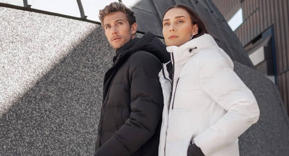 Man and woman pose while wearing winter jackets in an urban environment.