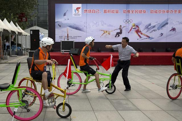 "In this Aug. 8, 2014 photo, cyclists prepare to take part in a carnival near a billboard promoting Beijing's bid for the 2022 Winter Olympics in Beijing. China, the new front-runner to host the 2022 Winter Olympics, doesn't have a long winter sports tradition; in fact, just 20 years ago, there were fewer than 10,000 skiers in the entire country - out of a then-population of 1.2 billion. The words on the board read: ""Set yourself alight, store your energy, promote exercise for everyone, promote Beijing Zhangjiakou bid for the Winter Olympics."" (AP Photo/Ng Han Guan)"