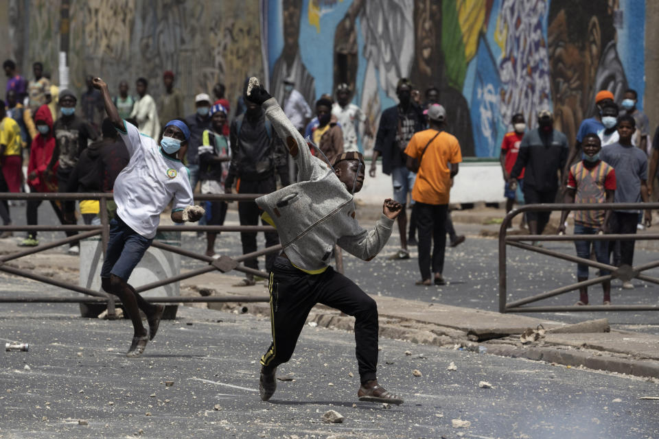 Demonstrators throw rocks at riot policemen during protests against the arrest of opposition leader and former presidential candidate Ousmane Sonko in Dakar, Senegal, Friday, March 5, 2021. Days of violent protests in Senegal have killed at least one person, local reports say, as young people take to the streets nationwide in support of the main opposition leader who was detained Wednesday. (AP Photo/Leo Correa)