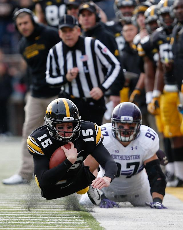 Iowa quarterback Jake Rudock (15) dives for a first down in front of Northwestern's Tyler Scott (97) during the first half of an NCAA college football game Saturday, Oct. 26, 2013, in Iowa City, Iowa. (AP Photo/Brian Ray)