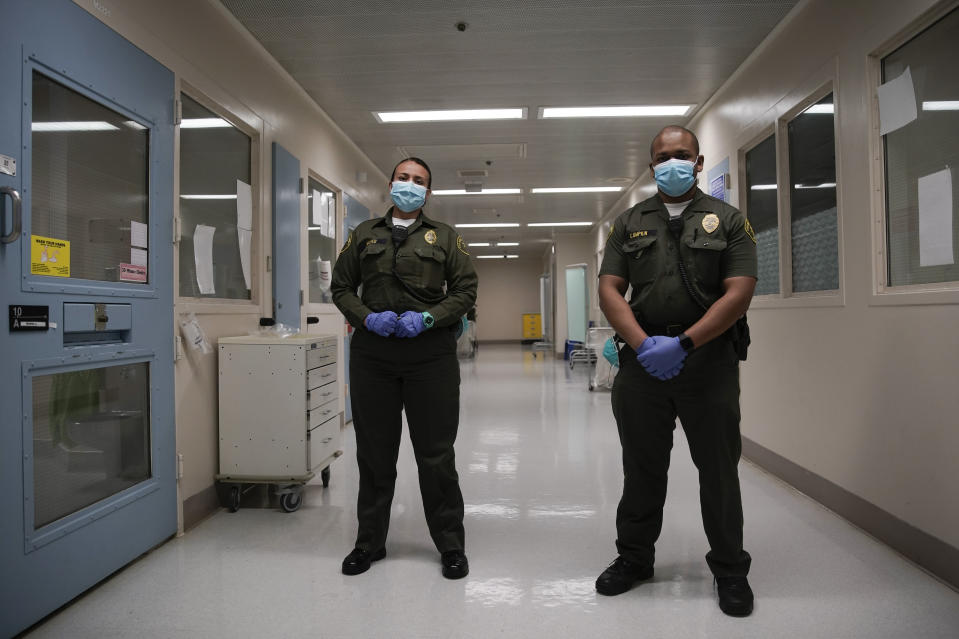 In this April 16, 2020, photo Sonia Munoz, left, and Christopher Lumpkin, custody assistants, poses for a picture at the hospital ward of the Twin Towers jail in Los Angeles. Across the country first responders who've fallen ill from COVID-19, recovered have begun the harrowing experience of returning to jobs that put them back on the front lines of America's fight against the novel coronavirus. (AP Photo/Chris Carlson)