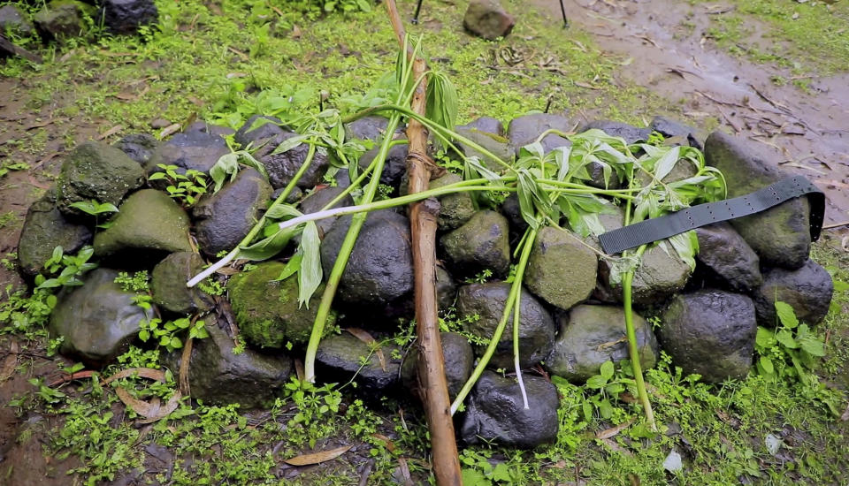 """In this image made from video, rocks and branches cover the makeshift graves of killed civilians, according to residents, in the village of Chenna Teklehaymanot, in the Amhara region of northern Ethiopia Thursday, Sept. 9, 2021. At the scene of one of the deadliest battles of Ethiopia's 10-month Tigray conflict, witness accounts reflected the blurring line between combatant and civilian after the federal government urged all capable citizens to stop Tigray forces """"once and for all."""" (AP Photo)"""
