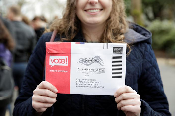 Lexi Menth of Seattle holds up a vote-by-mail ballot