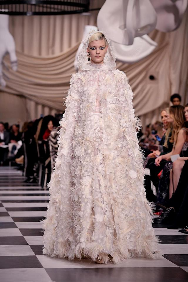 <p>A model wears a blush pink hooded gown with floral appliqués that mimics a look one might find in the dystopian show <em>The Handmaid's Tale.</em> (Photo: Getty) </p>