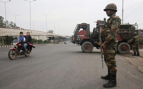 An Indian Army soldier stands guard as a family rides on a motorbike during a curfew in Jammu - Credit: Reuters