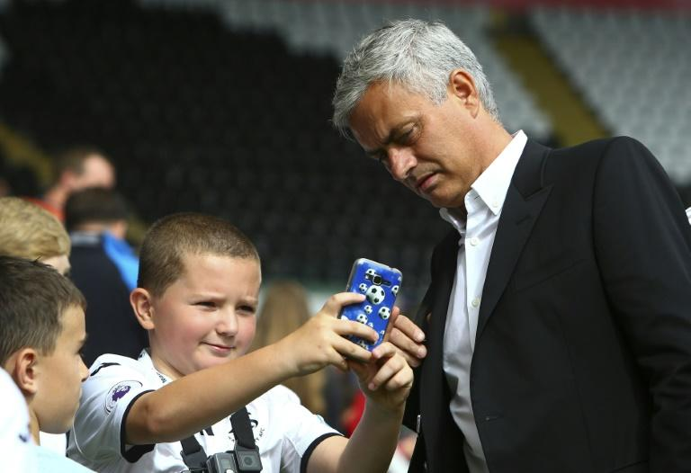 A young fan takes a photo with Manchester United's manager Jose Mourinho before the English Premier League match against Swansea City, at The Liberty Stadium in Swansea, south Wales, on August 19, 2017