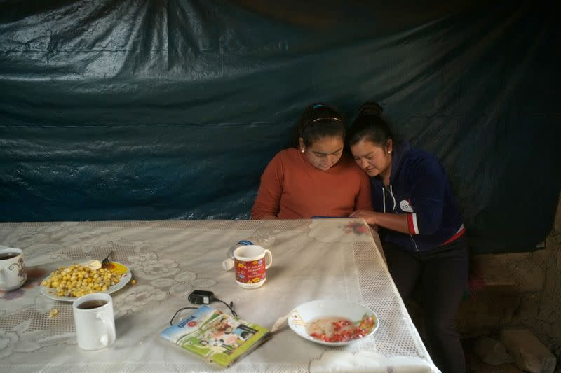 Luceli Banda Medina and her sister look at a tablet provided by their school, at their home, in Puna